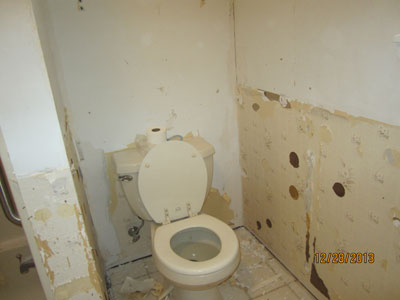 Hall bathroom with chair rail, bead wall and flooring taken out.